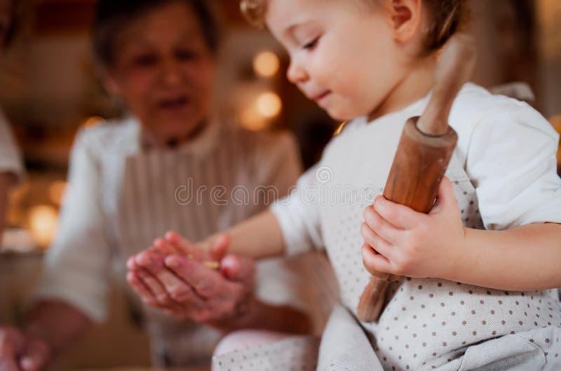 有在家做蛋糕的小小孩孙的资深祖母 免版税库存照片