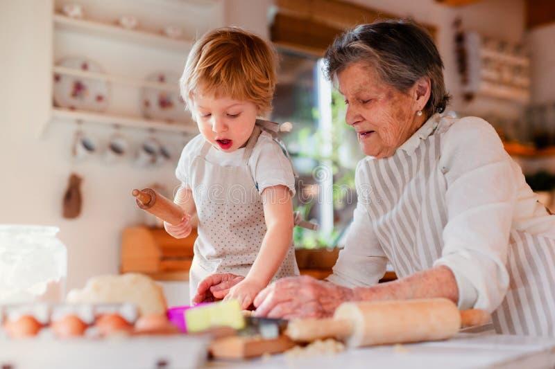 有在家做蛋糕的小小孩男孩的资深祖母 库存图片