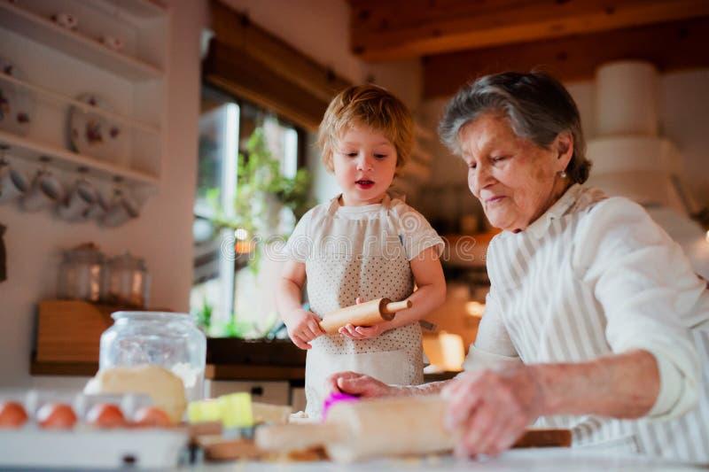 有在家做蛋糕的小小孩男孩的资深祖母 免版税库存图片
