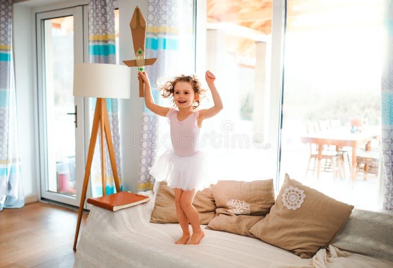 有在家公主礼服的一个小女孩,举行玩具剑和跳跃 免版税库存图片