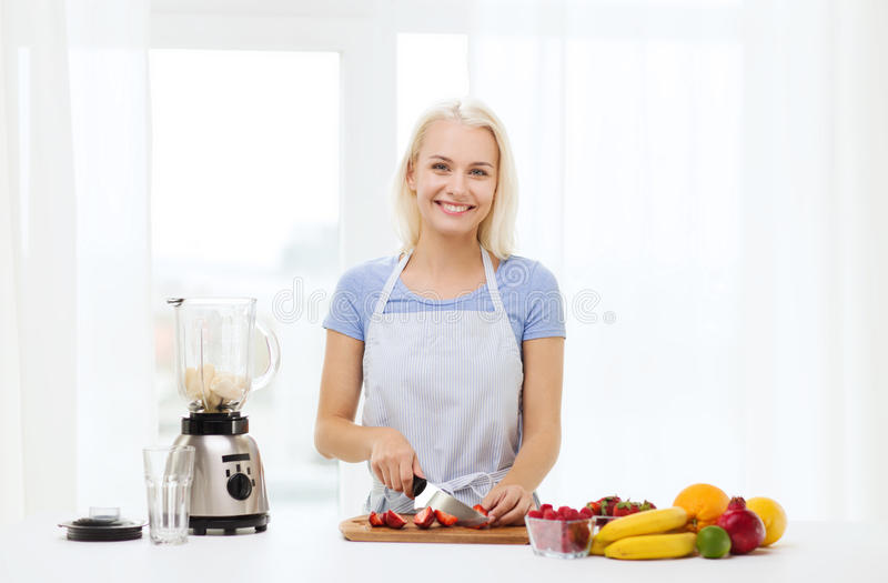 有在家准备震动的搅拌器的微笑的妇女 免版税库存照片