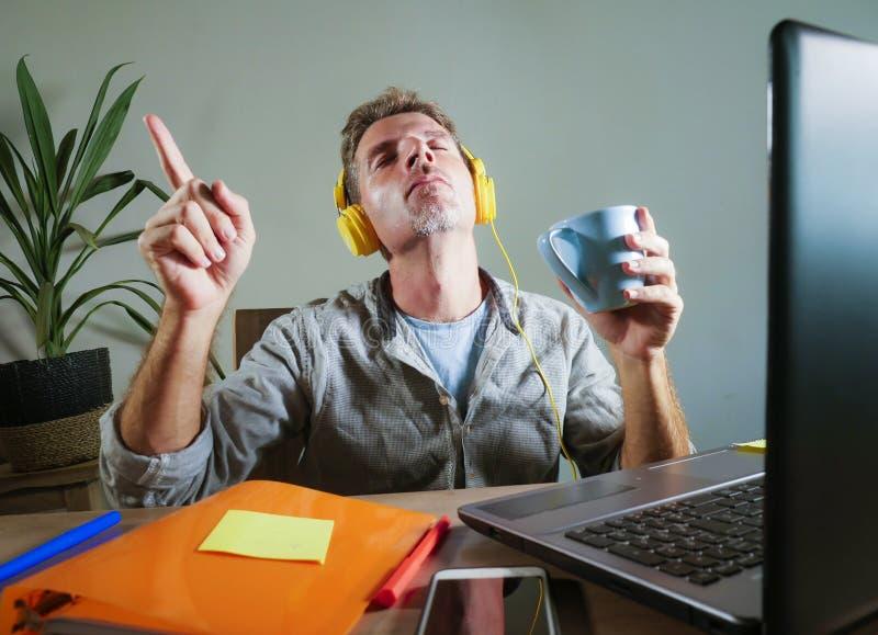 有在家坐办公桌的黄色耳机的年轻可爱和愉快的人与有的便携式计算机一起使用乐趣listenin 免版税库存图片