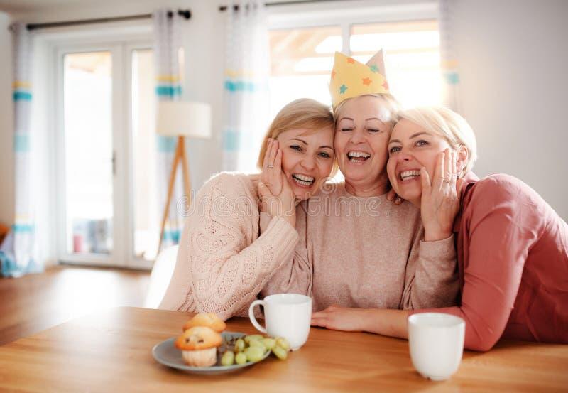 有在家坐在桌上的两个成人女儿的一个资深母亲,获得乐趣 免版税库存照片