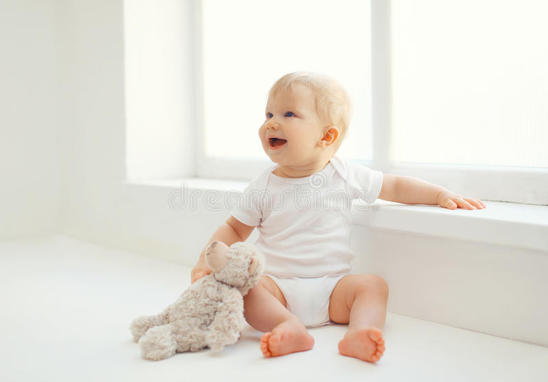 有在家坐玩具熊的玩具的逗人喜爱的微笑的婴孩 图库摄影