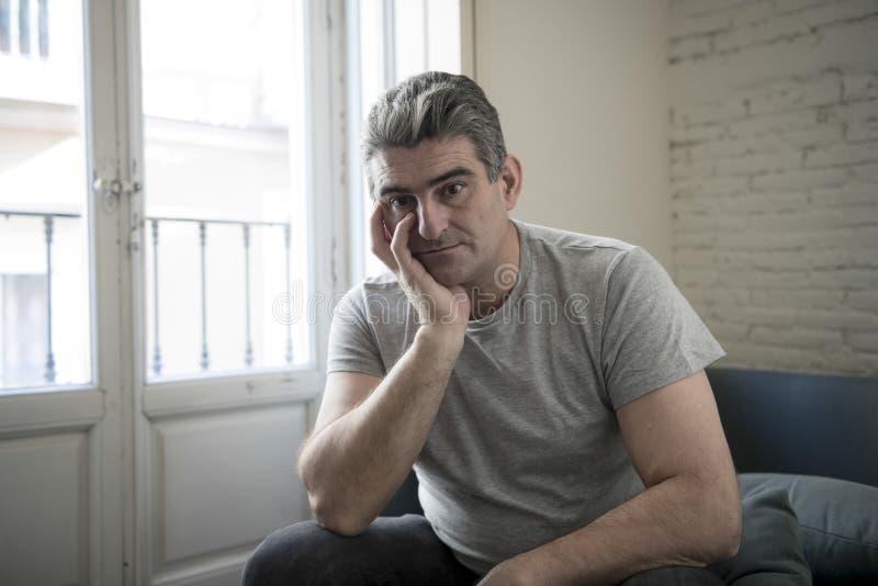 有在家坐长沙发看的灰色头发的哀伤和担心的人 免版税图库摄影
