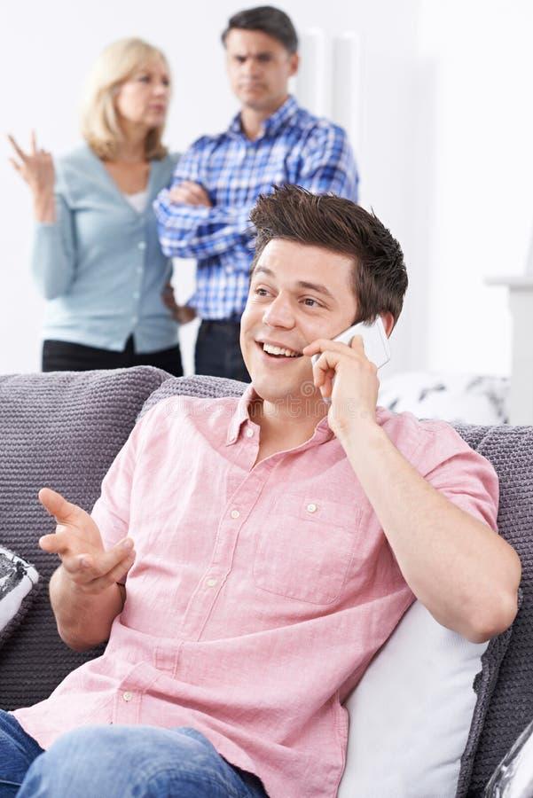 有在家居住成人的儿子的不快乐的成熟父母 免版税库存照片