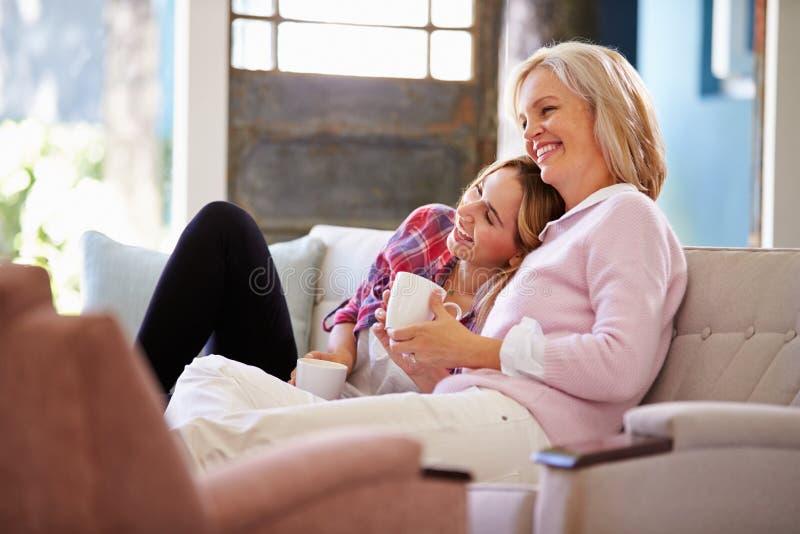 有在家看电视的成人女儿的成熟母亲 库存照片