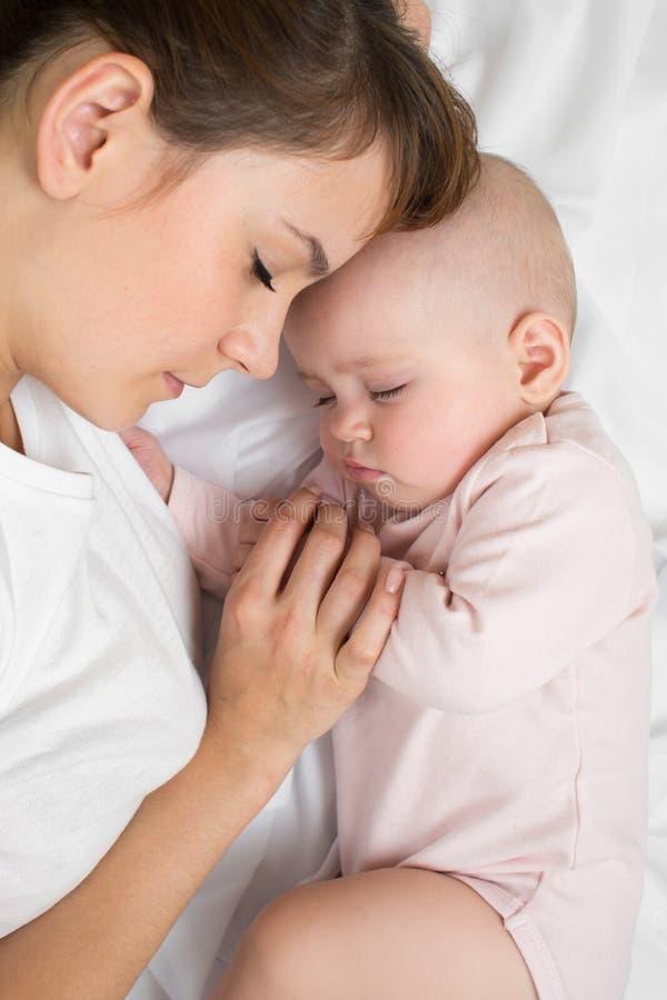 有在家睡觉在床上的新出生的婴孩的母亲 顶视图,关闭 免版税库存照片