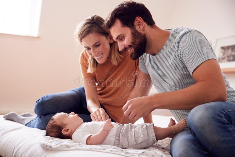 有在家说谎在床上的新生儿的慈爱的父母在顶楼公寓 免版税库存图片