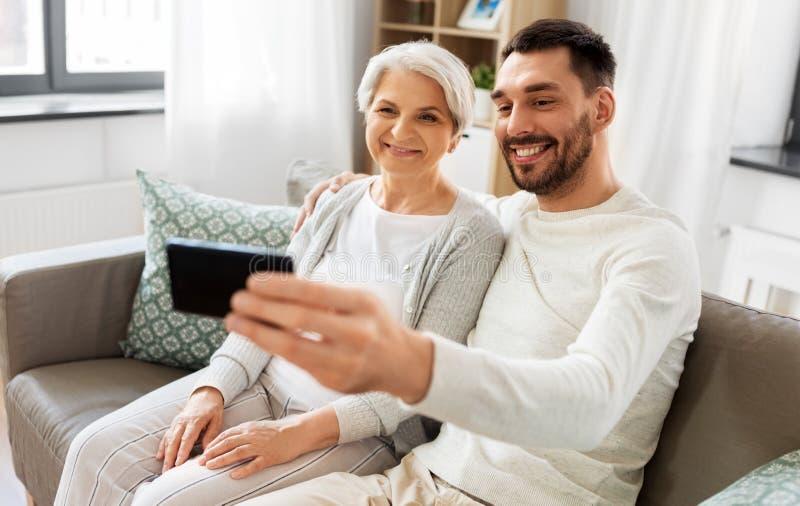 有在家采取selfie的成人儿子的资深母亲 免版税库存图片