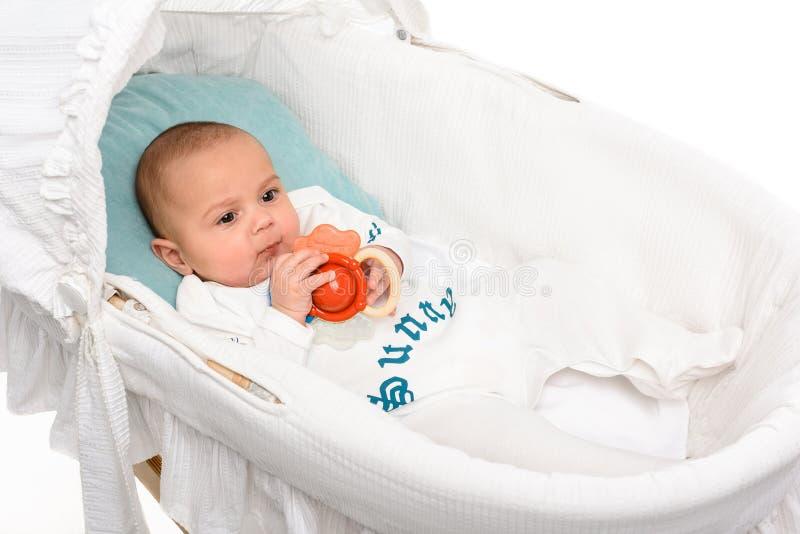 有在小儿床的玩具的逗人喜爱的矮小的婴孩 图库摄影