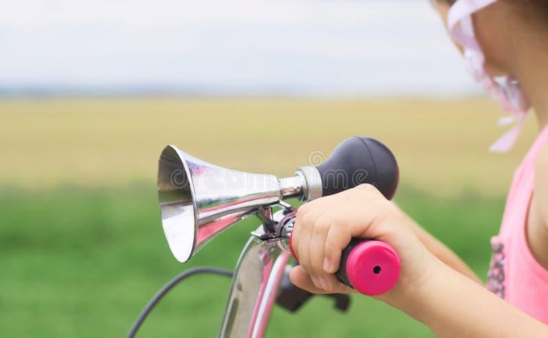 有在小孩子的自行车和黑橡胶电灯泡特写镜头的古板的垫铁登上的镀铬物喇叭 a的女孩 免版税库存图片