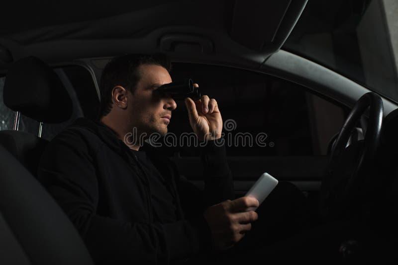 有在手中做监视的智能手机的男性无固定职业的摄影师由双筒望远镜从 免版税图库摄影