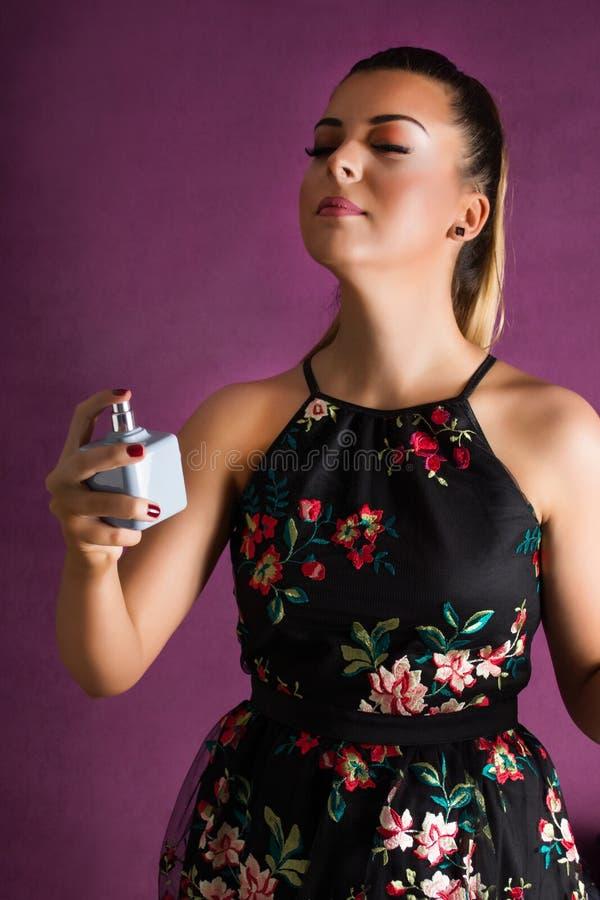 有在手中喷洒在她的在紫色背景的礼服的香水瓶的逗人喜爱的女孩 免版税库存图片