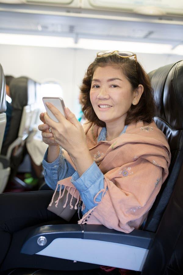 有在手中坐在空中飞机位子p的巧妙的电话的亚裔妇女 库存照片