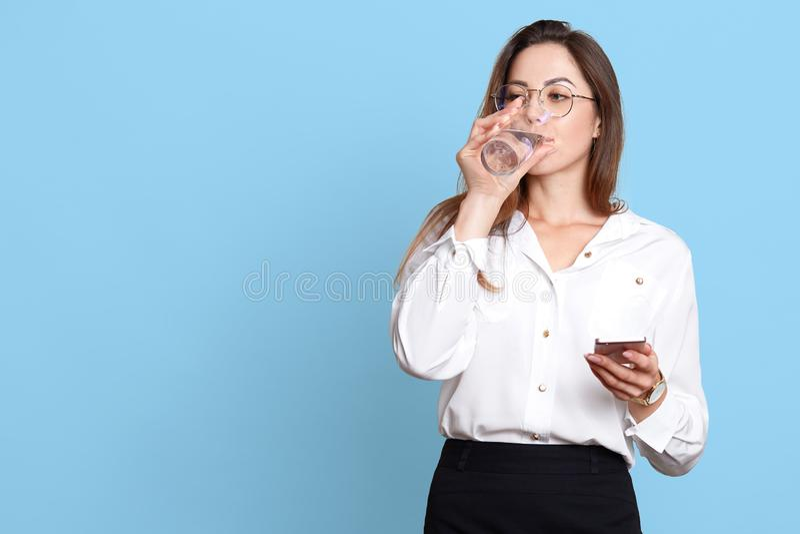 有在手中拿着手机和喝净水的健康皮肤的美丽的年轻女人,当有企业交谈,时 免版税图库摄影