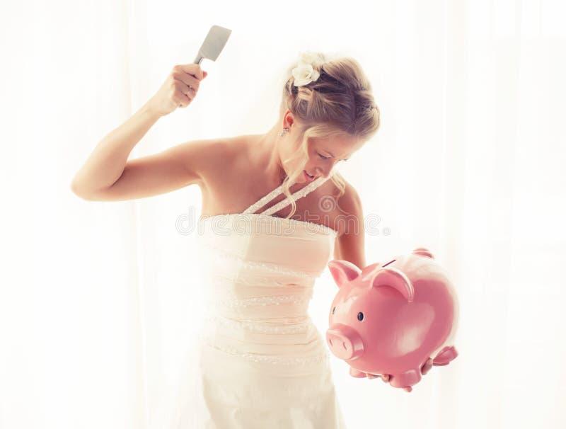 有在手中捣毁存钱罐的刀子的恼怒的新娘 免版税库存图片