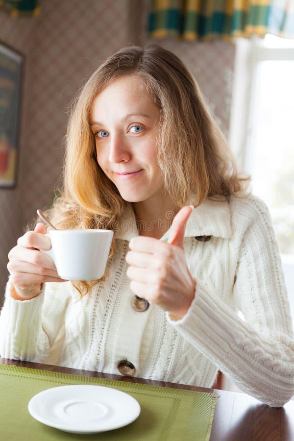 有在手中显示赞许标志的一杯咖啡的少妇 免版税库存图片
