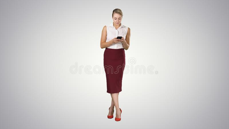 有在手中智能手机的可爱的欧洲女性,有手指的触摸屏键入在梯度背景的消息 免版税图库摄影