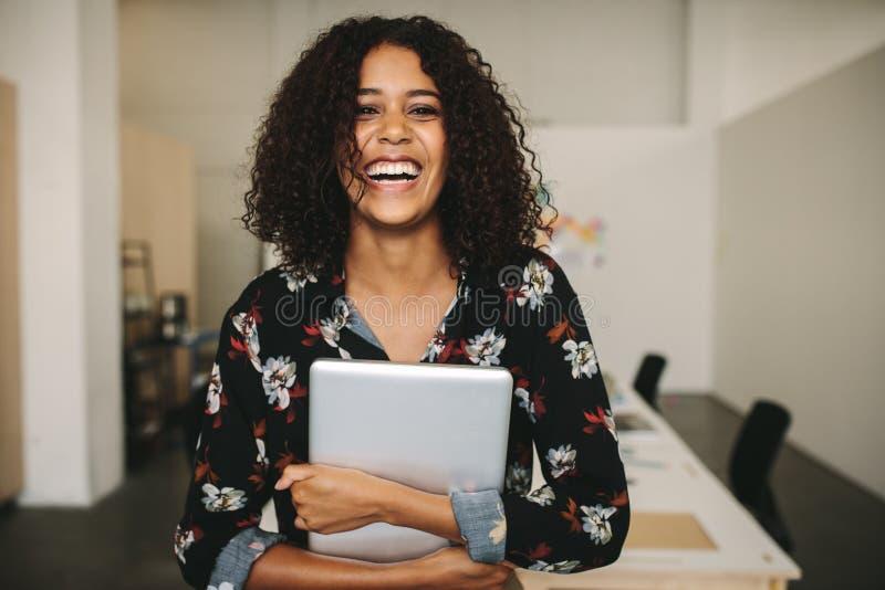 有在手中站立在办公室的膝上型计算机的女实业家 免版税库存图片
