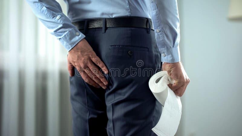 有在手中遭受痔疮痛苦,腹泻的卫生纸的办公室工作者 免版税图库摄影