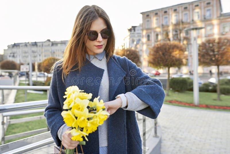 有在手边看时钟的黄色春天花花束的美女,背景都市样式 图库摄影