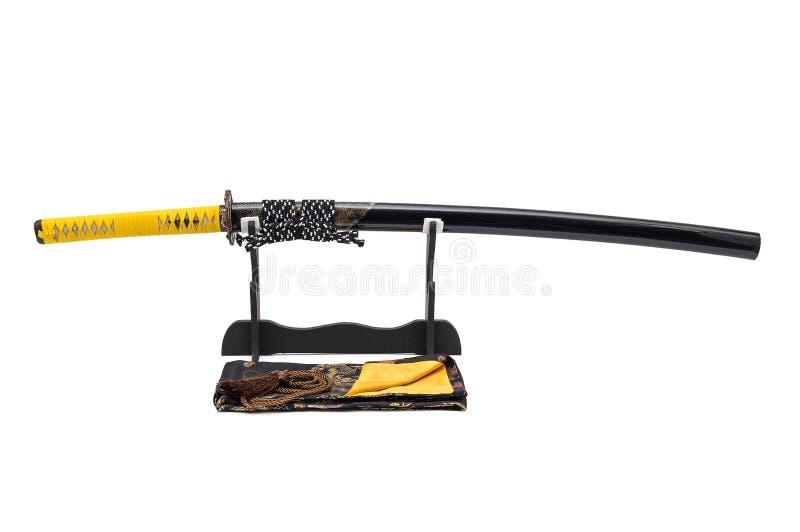 有在把柄和刀鞘包裹的黄色皮革绳子的日本剑有光芒皮肤的在立场白色背景,黑丝绸袋子在 图库摄影