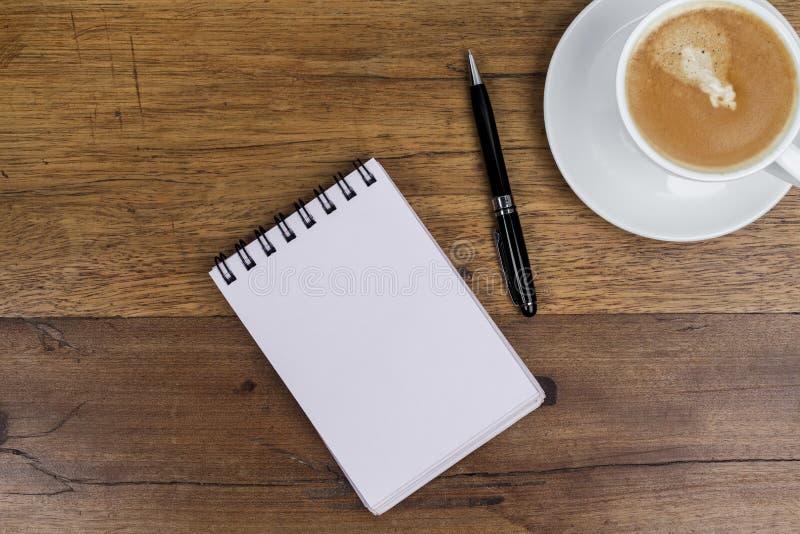有在旁边笔的在木桌上的笔记本和咖啡 库存图片
