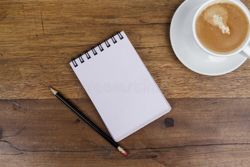 有在旁边铅笔和咖啡的笔记本在木桌上 库存图片