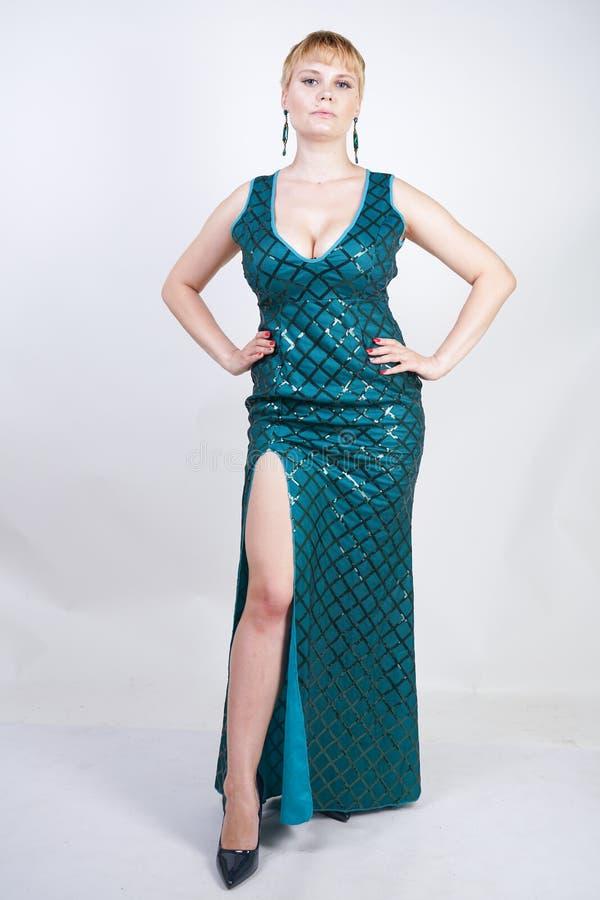 有在有衣服饰物之小金属片和立场的一件豪华长的晚上绿色礼服穿戴的短的金发的迷人的年轻正大小妇女在a 图库摄影