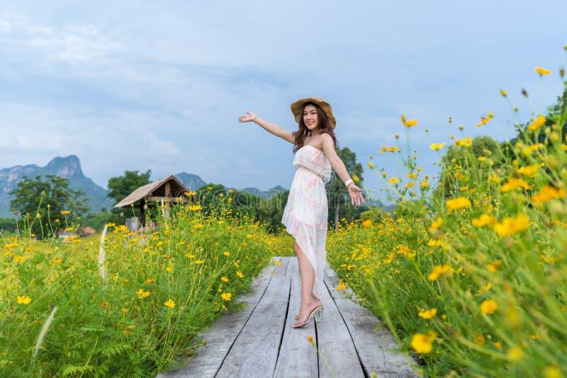 有在有黄色波斯菊花田的木桥举的胳膊的妇女 免版税图库摄影