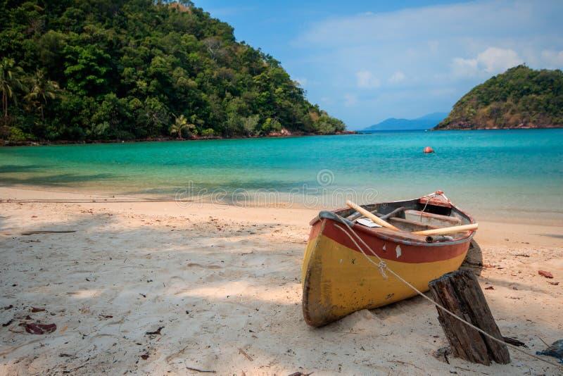 有在沙子的一个老橙色独木舟 库存照片