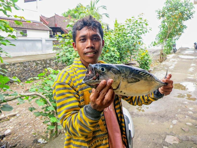 有在海捉住的金枪鱼的一位年轻渔夫 一位年轻印度尼西亚渔夫的一开心 鲜美鱼用精美肉 Sunn 免版税库存照片