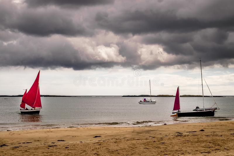 有在海滩被停泊的红色风帆的帆船 免版税库存照片
