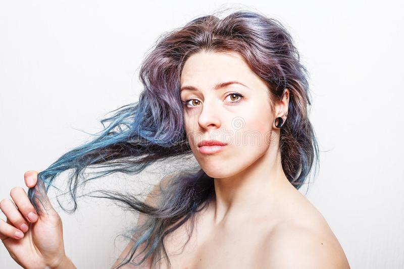 有在淡色口气上色的损坏的头发的少妇 免版税库存图片