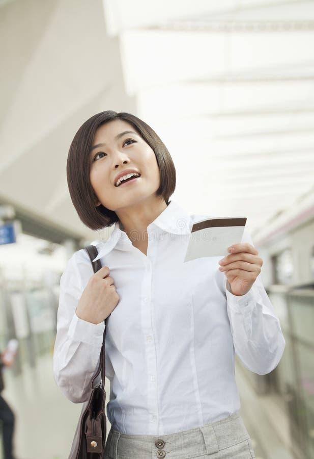 有在火车站,北京的激动的少妇一张火车票 免版税库存照片