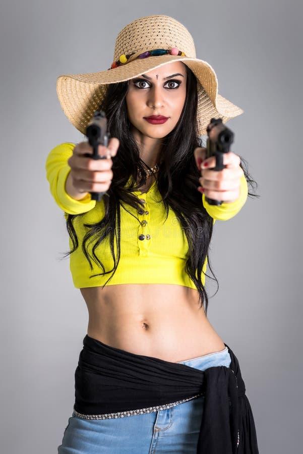 有在灰色背景隔绝的枪的时兴的女孩 免版税库存照片