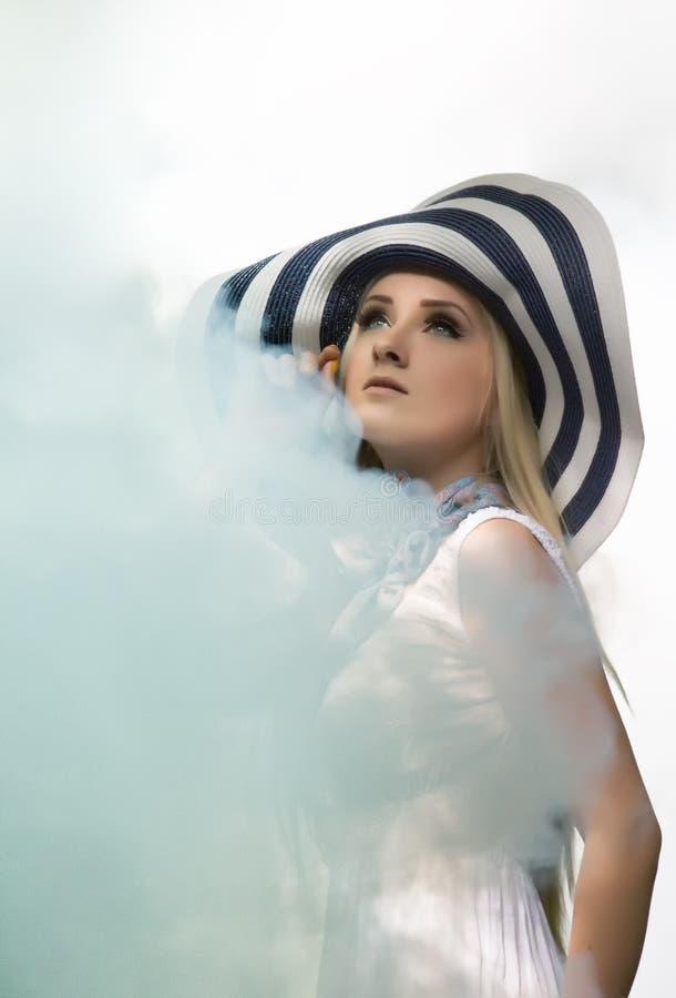 有在烟和一件白色礼服的美丽的年轻白肤金发的女孩盖的一个镶边帽子 库存图片