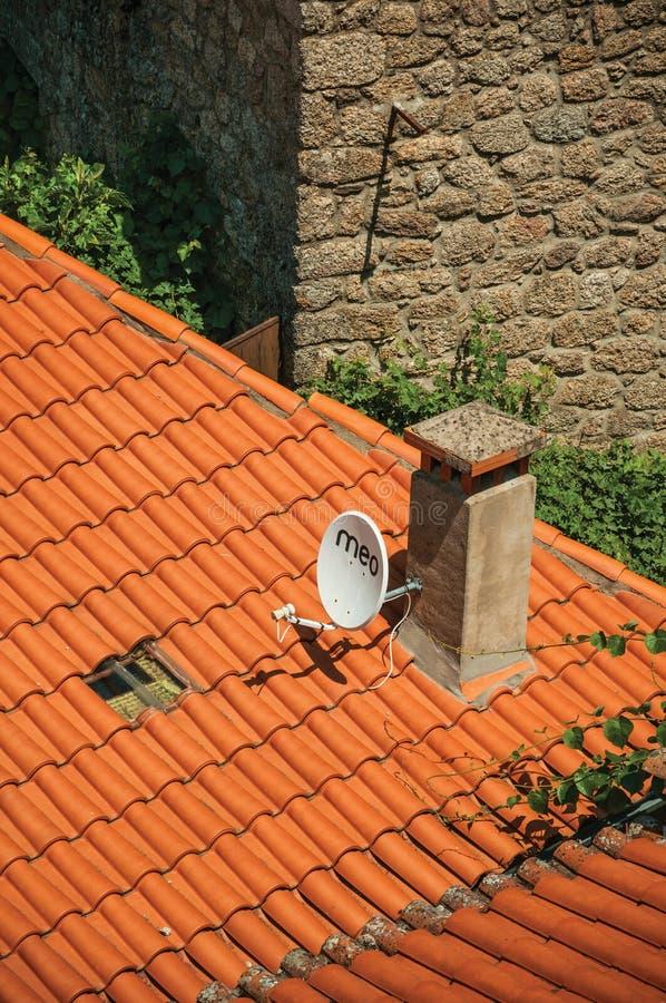 有在烟囱困住的抛物面天线的议院屋顶 图库摄影