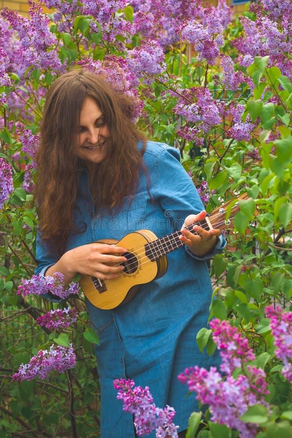 有在牛仔布礼服穿戴的卷发的少女播放在开花的丁香背景的尤克里里琴  库存照片