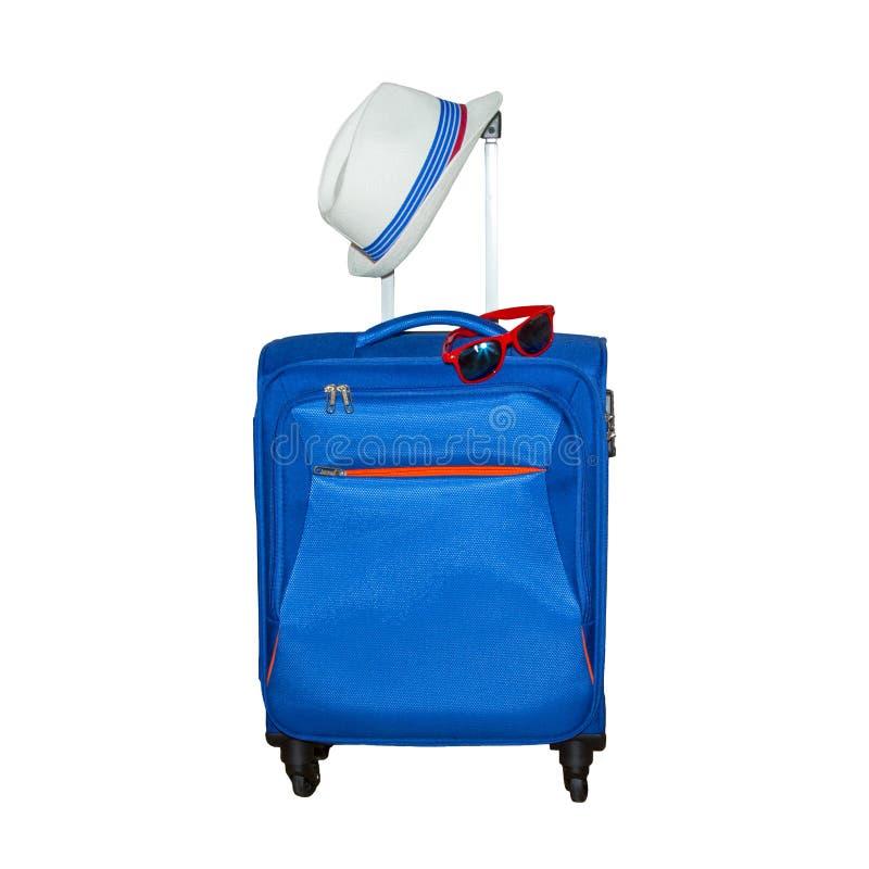 有在白色背景和时兴的太阳镜的蓝色手提箱隔绝的夏天帽子 暑假旅行概念 图库摄影