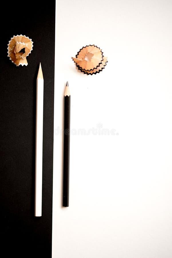有在白色背景隔绝的削片的黑白铅笔 大下落绿色叶子宏观摄影水 顶视图 免版税库存照片