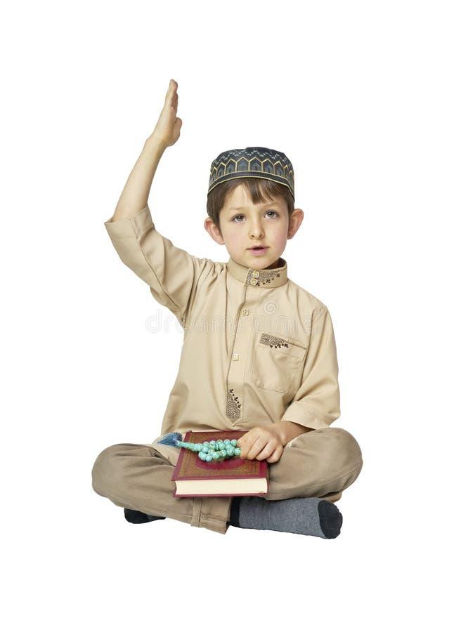 有在白色背景隔绝的古兰经的小男孩 库存图片