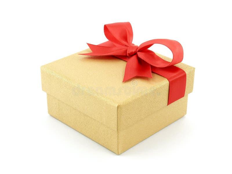 有在白色背景隔绝的红色丝带弓的金黄礼物盒 免版税库存图片