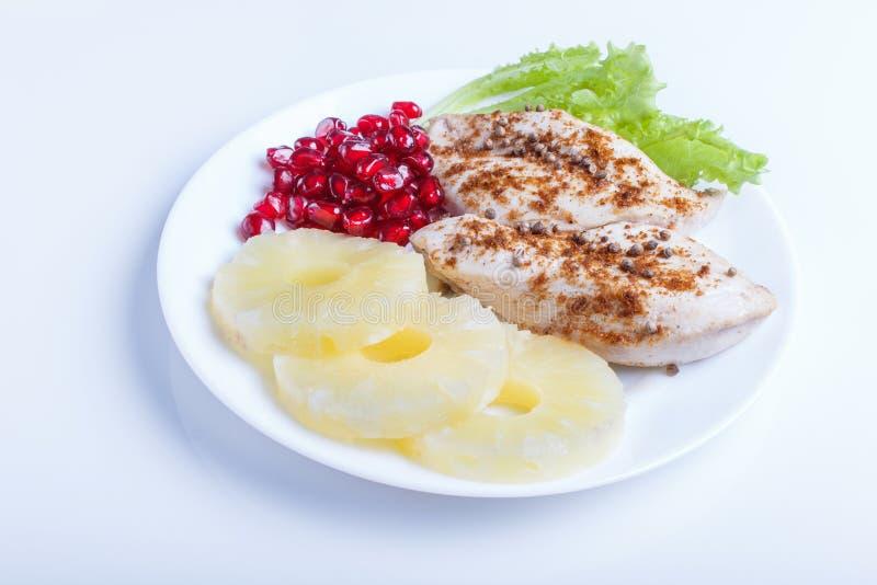 有在白色背景隔绝的莴苣、菠萝和石榴种子的炸鸡内圆角 图库摄影