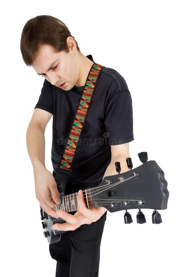 有在白色背景隔绝的电吉他的年轻人 每 库存照片