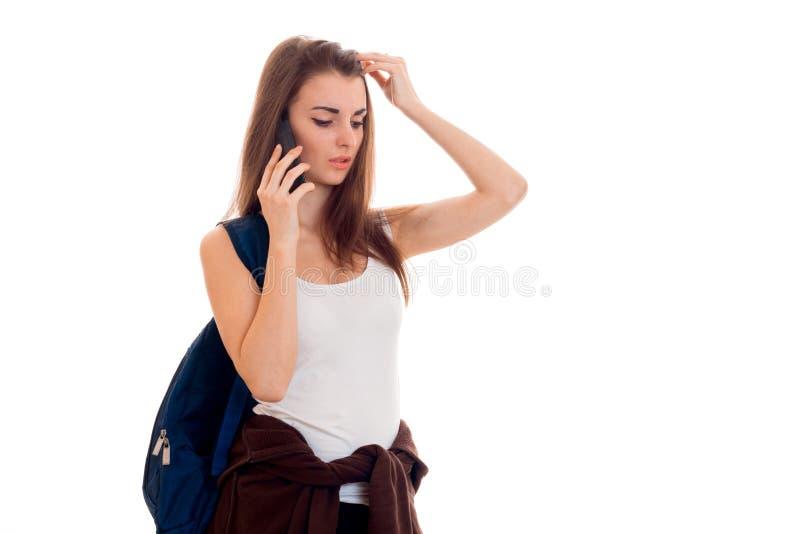 有在白色背景隔绝的背包谈的电话的秀丽年轻深色的学生女孩 库存照片
