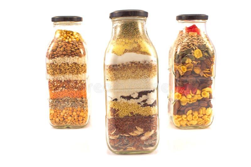 有在白色隔绝的各种各样的种子的装饰玻璃瓶图片
