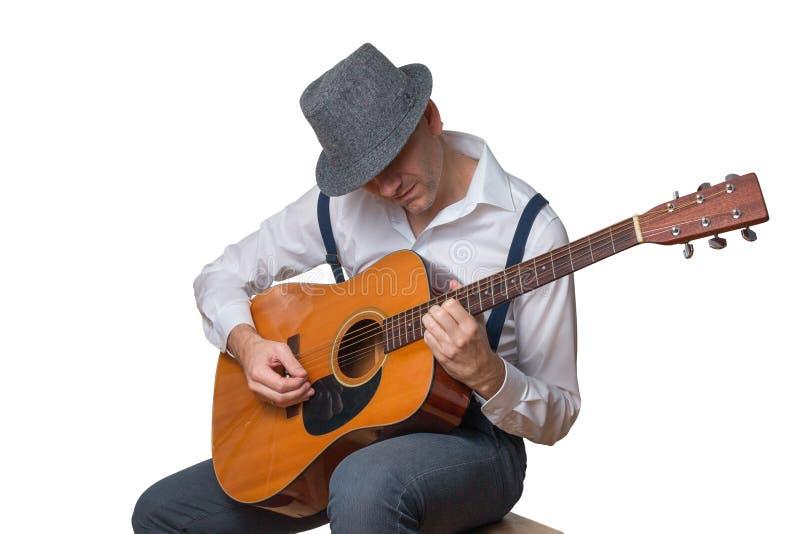 有在白色隔绝的声学吉他佩带的帽子的人 免版税库存照片