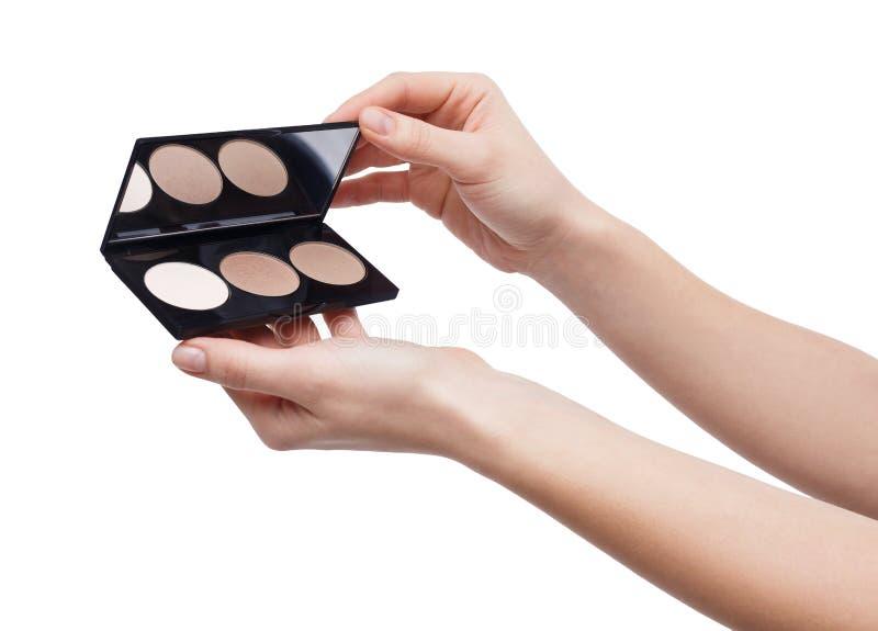 有在白色隔绝的棕色眼影膏调色板的妇女 库存照片